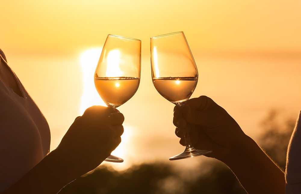 A couple enjoys a sunset with wine from a Cambria wine tasting